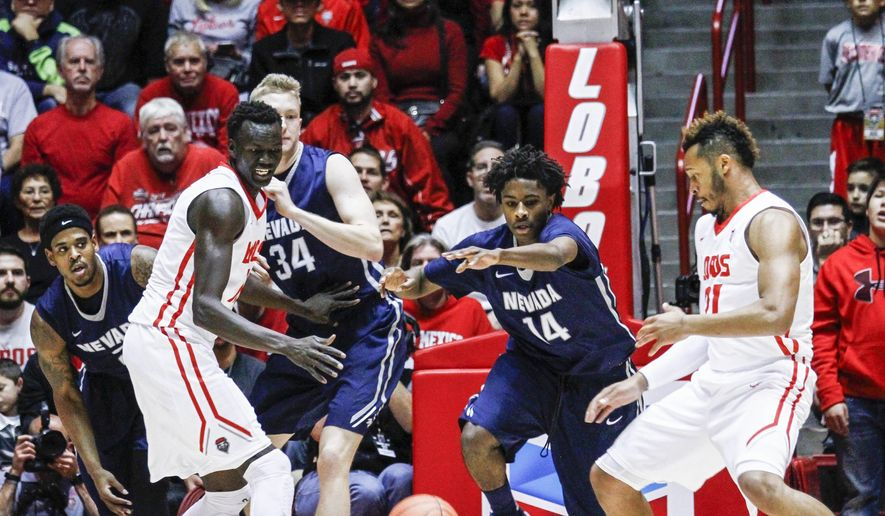 Nevada's Lindsey Drew (14) and New Mexico's Obij Aget (11) and Xavier Adams chase down a loose ball during the first half an NCAA college basketball game Wednesday, Dec. 30, 2015, in Albuquerque, N.M. (AP Photo/Juan Labreche)