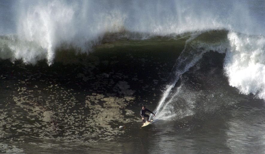 FILE - In this Dec. 21, 2005 file photo, a surfer takes on a huge wave at Lunada Bay in Palos Verdes Estates, Calif. JeffKepley, the city's new police chief, is vowing to crack down on locals accused of using violence and intimidation to protect their surf spot from intrusion by outsiders. Authorities have been accused of looking the other way for decades as local surfers at Lunada Bay threatened outsiders, hurled rocks at them and vandalized their cars. (Sean Hiller/South Bay Daily Breeze via AP, File)
