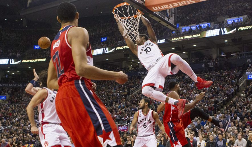 Toronto Raptors' DeMar DeRozan hangs from the hoop as he watches the path of the ball after being fouled by Washington Wizards' Garrett Temple, right, during the first half an NBA basketball game in Toronto on Wednesday, Dec. 30, 2015. (Chris Young /The Canadian Press via AP) MANDATORY CREDIT