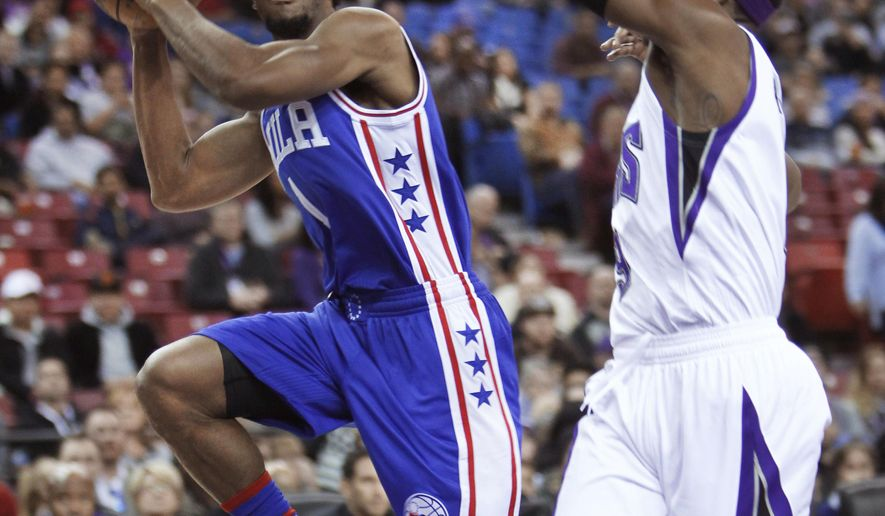 Philadelphia 76ers guard Ish Smith, left, shoots around Sacramento Kings defender Rajon Rondo during the first half of an NBA basketball game in Sacramento, Calif., on Wednesday, Dec. 30, 2015.(AP Photo/Steve Yeater)