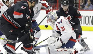 Washington Capitals goalie Philipp Grubauer (31), of Germany, defends the goal against Carolina Hurricanes' Jordan Staal (11) and Brett Pesce (54) during the second period of an NHL hockey game in Raleigh, N.C., Thursday, Dec. 31, 2015. (AP Photo/Gerry Broome)