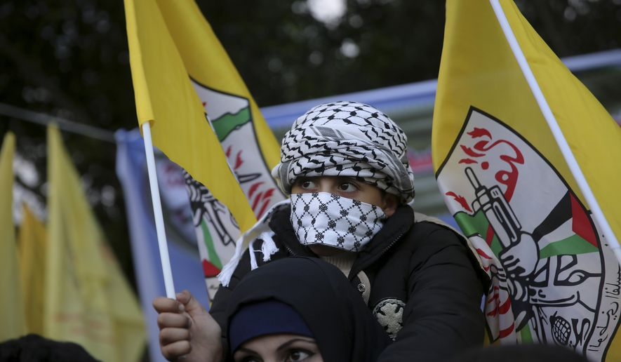 A Palestinian woman carries her masked son while waving a yellow Fatah flag during a rally to commemorate the 51st anniversary of the Fatah movement, at the Unknown Soldier Square in Gaza City, Thursday, Dec. 31, 2015. Gaza's Hamas rulers have outlawed all New Year's celebrations in Gaza this year. (AP Photo/Adel Hana)