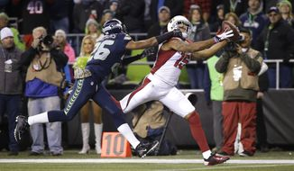 FILE- In this Nov. 15, 2015, file photo, Arizona Cardinals wide receiver Michael Floyd catches a pass for a touchdown as Seattle Seahawks cornerback Cary Williams defends during the first half of an NFL football game in Seattle. On a Sunday night seven weeks ago, th Cardinals pulled off a 39-32 victory over the Seahawks. They haven't lost since. Now both teams are firmly in the playoffs, with seeding all that's at stake when they meet in their regular-season finale on Sunday. (AP Photo/Elaine Thompson, File)