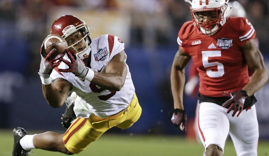 Southern California wide receiver JuJu Smith-Schuster (9) drops a pass as Wisconsin cornerback Darius Hillary (5) defends during the first half of the Holiday Bowl NCAA college football game Wednesday, Dec. 30, 2015, in San Diego. (AP Photo/Gregory Bull)
