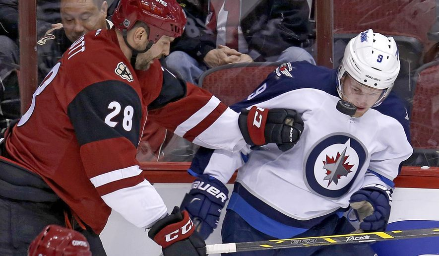 Arizona Coyotes left wing John Scott (28) and Winnipeg Jets center Andrew Copp battle for the puck in the first period during an NHL hockey game, Thiursday, Dec. 31, 2015, in Glendale, Ariz. (AP Photo/Rick Scuteri)
