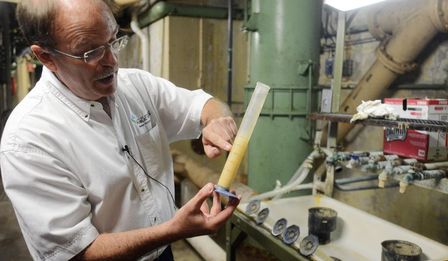 In this Monday, June 1, 2015 photo, Tim Stefanich, environmental engineer at the Sioux Falls water purification plant, shows how solids fall out of suspension after adding lime during the first step of the purification process during a tour at the plant in Sioux Falls, S.D. New fluoride standards will save water treatment plants in South Dakota a total of about $400,000 a year, state officials say. (Elisha Page/The Argus Leader via AP) MANDATORY CREDIT