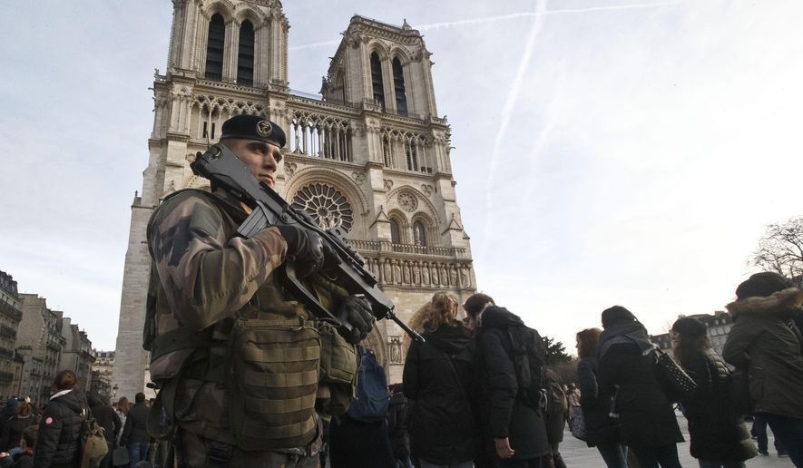 A soldier patrols at the Notre Dame cathedral in Paris, Wednesday, Dec. 30, 2015. France's defense minister has visited troops on duty ahead of unusually tense New Year's Eve celebrations in Paris after November attacks that left 130 dead and hundreds injured. (AP Photo/Michel Euler)