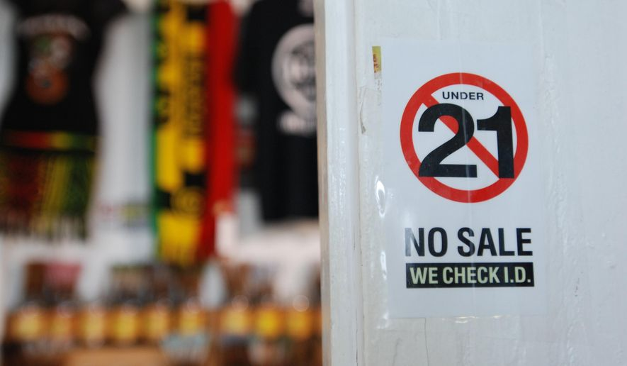 In this Tuesday, Dec. 29, 2015, photo, retailer Holy Smokes has signs posted around its entryway to alert customers to the state's new smoking laws in Honolulu. (AP Photo/Cathy Bussewitz)