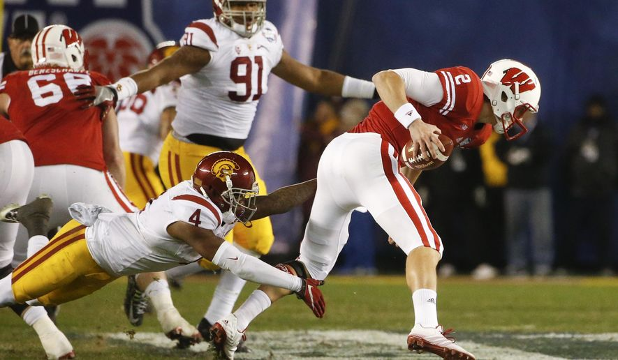 Wisconsin quarterback Joel Stave (2) escapes Southern California safety Chris Hawkins (4) during the first half of the Holiday Bowl NCAA college football game Wednesday, Dec. 30, 2015, in San Diego. (AP Photo/Lenny Ignelzi)