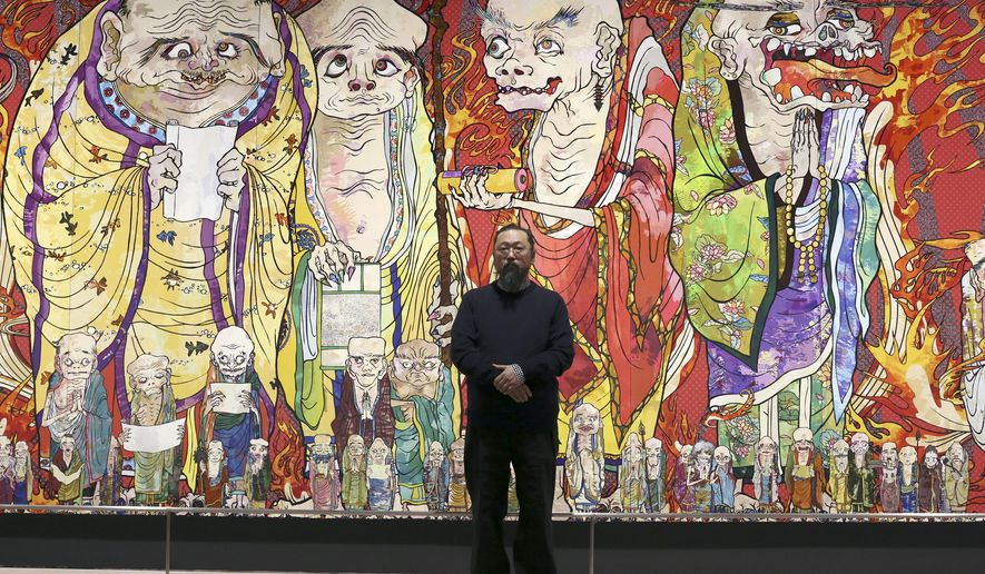 "In this Dec. 29, 2015 photo, Japanese artist Takashi Murakami poses in front of part of his work titled ""The 500 Arhats"" exhibited at Mori Art Museum in Tokyo. In the gentrified kitsch landscape Murakami depicts, 500 grotesque priests parade along dazzlingly colorful giant panels. (AP Photo/Eugene Hoshiko)"