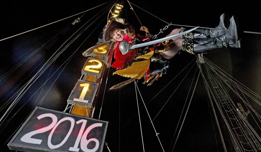 """In this Wednesday, Dec. 30, 2015, photo provided by the Florida Keys News Bureau,  Evalena Worthington, garbed in a pirate wench costume, practices her New Year's Eve descent from the top of a sailing ship's mast at the Schooner Wharf Bar in Key West, Fla. Beginning late Thursday, Dec. 31, Worthington is to be lowered as one of four unique """"drops"""" in Key West to mark the beginning of 2016. Other planned Florida Keys iconic descents include a large replica of a conch shell, a fake Key lime wedge into a giant margarita glass and a female impersonator in a large faux women's high heel. (Rob O'Neal/Florida Keys News Bureau via AP)"""