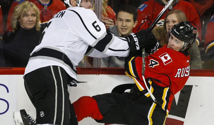 Los Angeles Kings' Jake Muzzin, left, checks Calgary Flames' Kris Russell during the third period of an NHL hockey game in Calgary, Alberta on Thursday, Dec. 31, 2015. (Jeff McIntosh/The Canadian Press via AP) MANDATORY CREDIT