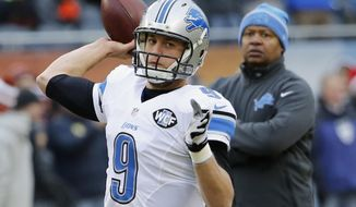 FILE - In this Dec. 21, 2014, file photo, Detroit Lions quarterback Matthew Stafford warms up as coach Jim Caldwell watches before an NFL football game against the Chicago Bears in Chicago. The Bears and the Lions meet again on Sunday, Jan. 3. (AP Photo/Charles Rex Arbogast, File)