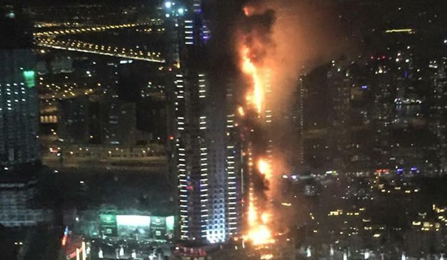 In this photo provided by Trevor Hale, smoke and flames pour out from a residential building as a fire runs up some 20 stories of the high rise in Dubai, United Arab Emirates, Thursday, Dec. 31, 2015. Fire engulfed the luxury building near the world's tallest skyscraper in Dubai on Thursday as tens of thousands of people were gathering at its base for one of the world's largest New Year's fireworks displays. (Trevor Hale via AP)