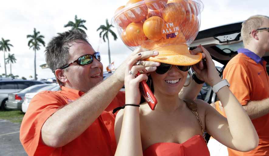 Marty Osborne, of Greenville, S.C., left, tries a hat adorned with oranges on Olivia Dietrich, of New York, before the Orange Bowl NCAA college football semifinal playoff game between Clemson and Oklahoma, Thursday, Dec. 31, 2015, in Miami Gardens, Fla. (AP Photo/Lynne Sladky)