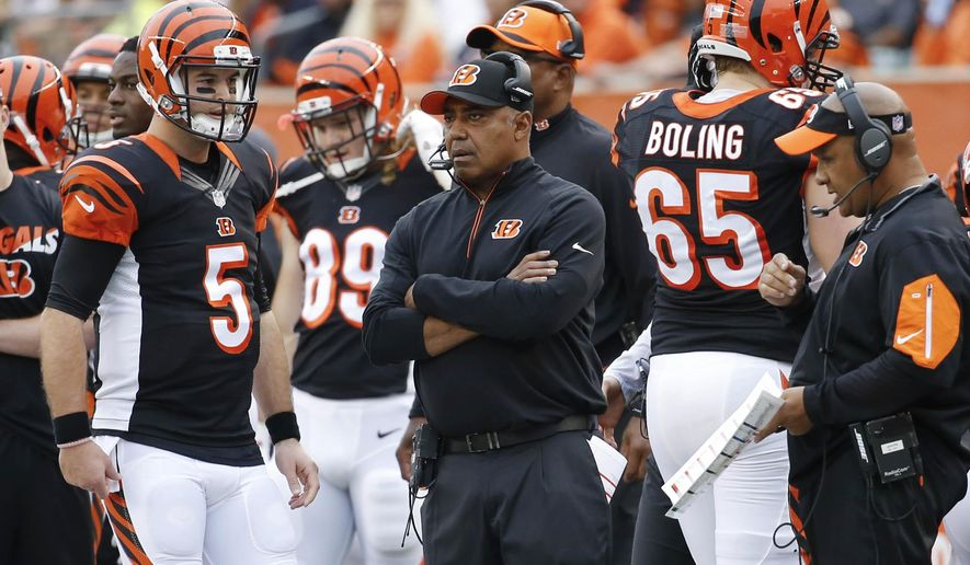 FILE - In this Sunday, Dec. 13, 2015 file photo, Cincinnati Bengals head coach Marvin Lewis, center, stands on the sideline along quarterback AJ McCarron (5) and offensive coordinator Hue Jackson, right, in the first half of an NFL football game against the Pittsburgh Steelers in Cincinnati. The Bengals play the Baltimore Raves on Sunday, Jan. 3. (AP Photo/Frank Victores, File)