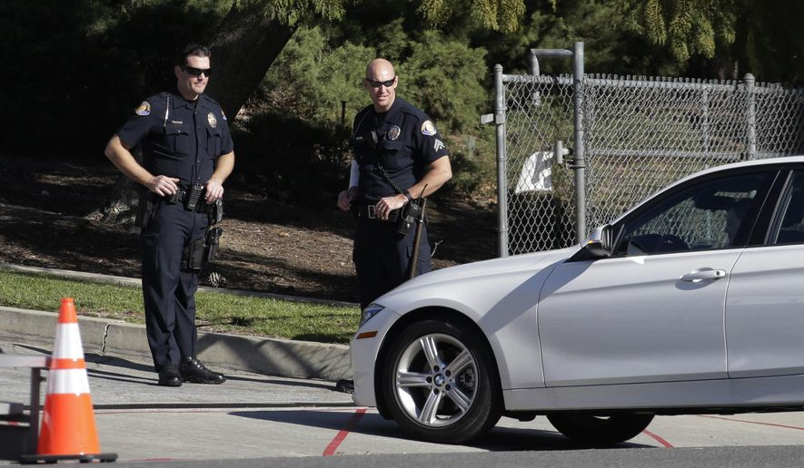 Two Pasadena police officers inspect a vehicle on Colorado Blvd on the route of the Rose Parade in Pasadena, Calif., Thursday, Dec. 31, 2015. Final preparations were underway Thursday for the 127th Rose Parade and 102nd Rose Bowl football game, the huge New Year's celebration that authorities said would be held under unprecedented security although there were no known threats. (AP Photo/Nick Ut)