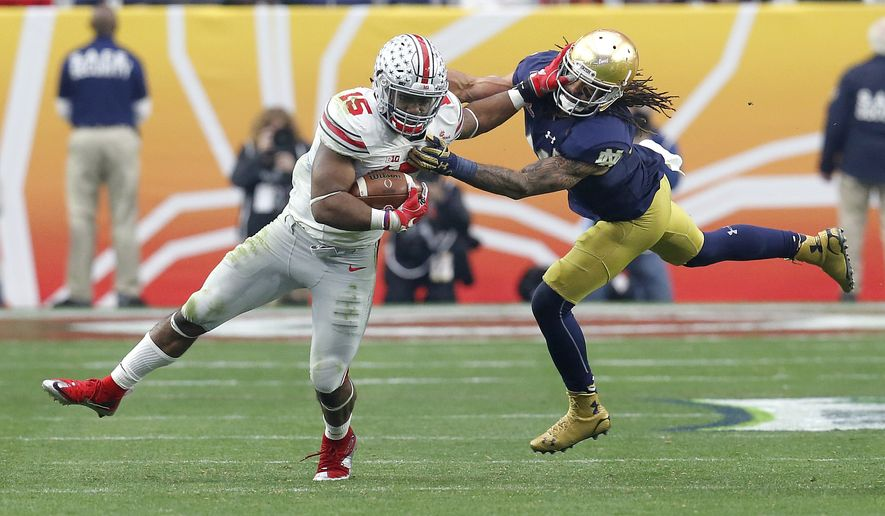 Ohio State running back Ezekiel Elliott (15) breaks free from Notre Dame cornerback Matthias Farley during the second half of the Fiesta Bowl NCAA College football game, Friday, Jan. 1, 2016, in Glendale, Ariz.  (AP Photo/Rick Scuteri)
