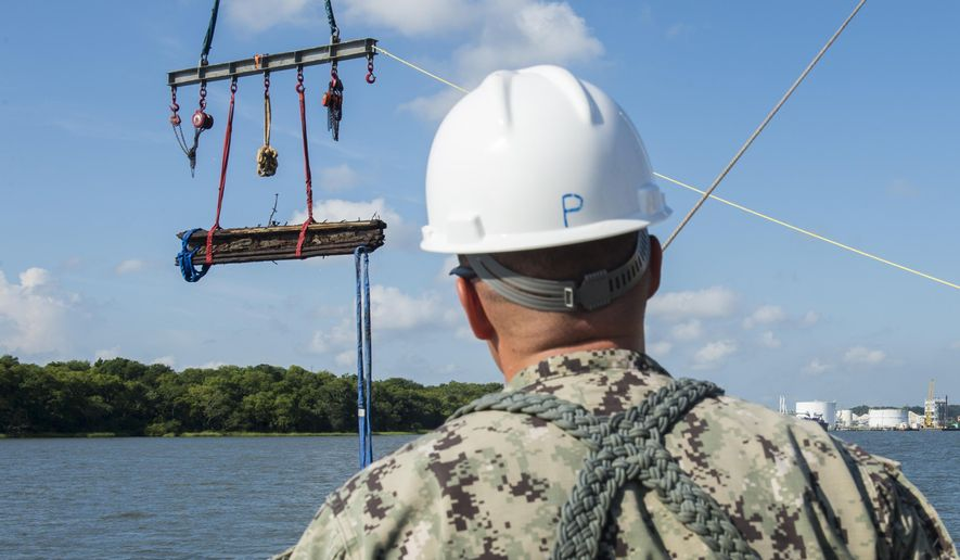 FILE- In this Aug. 14, 2015 file photo provided by the US Navy, Chief Warrant Officer 3, Jason Potts, on scene commander for Task Element CSS Georgia, supervises as a piece of casemate, made of railroad ties and timber, which served as the outer layer of armor for CSS Georgia, is raised from the Savannah River in Savannah, Ga. After the government spent months recovering wreckage of the sunken gunship, roughly half of the nearly 30,000 artifacts discovered has been returned to the bottom of the Savannah River. (MC1 Blake Midnight/US Navy via AP, File)