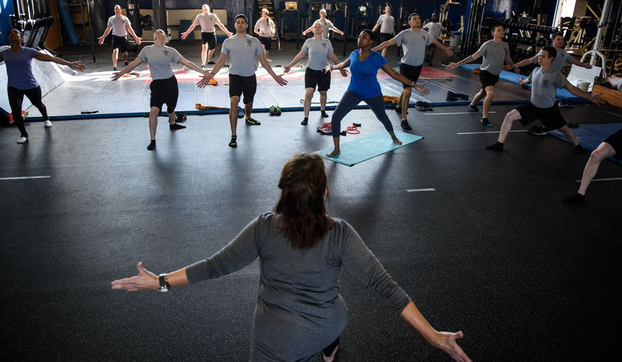 ADVANCE FOR USE SATURDAY, JAN. 2 AND THEREAFTER - Emily Meyer leads a yoga class of police recruit trainees Friday, Nov. 20, 2015, at the Fayetteville, N.C., Police Training Center. Fayetteville police recruits didn't expect yoga when they began law enforcement training. (Andrew Craft/The Fayetteville Observer via AP)