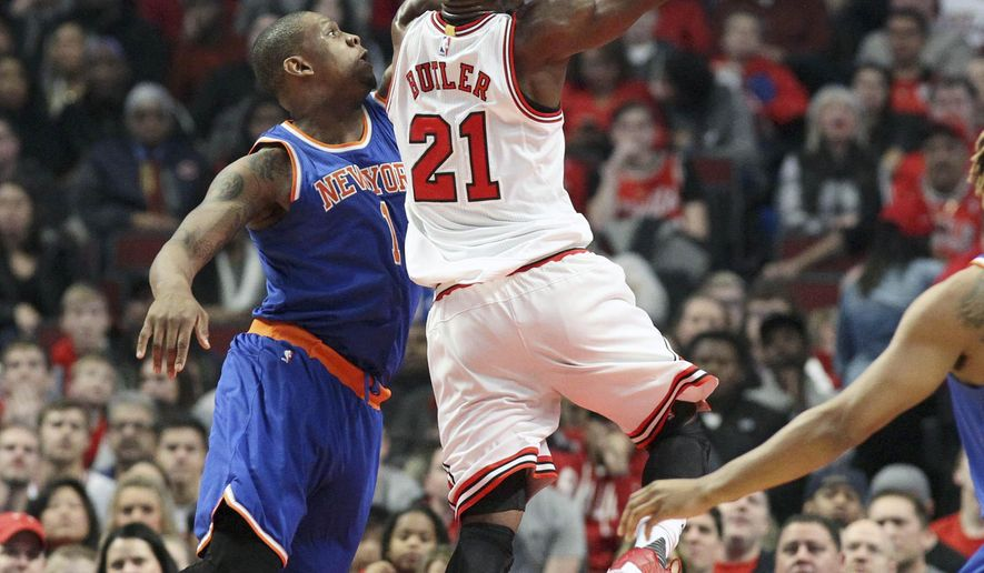 Chicago Bulls guard Jimmy Butler (21) drives the lane past New York Knicks center Kevin Seraphin (1) during the first half of an NBA basketball game in Chicago, on Friday, Jan. 1, 2016. (AP Photo/Jeff Haynes)