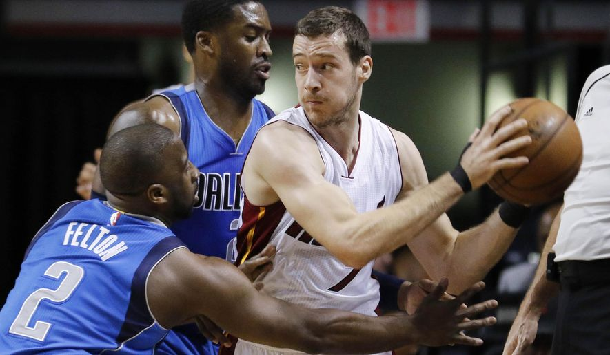 Miami Heat guard Goran Dragic (7) is pressured by Dallas Mavericks guard Raymond Felton (2) and guard Wesley Matthews (23) in the first quarter of an NBA basketball game, Friday, Jan. 1, 2016, in Miami. (AP Photo/Joe Skipper)