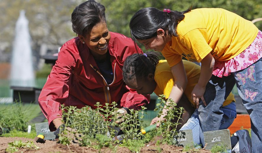 FILE - In this April 9, 2009 file photo, first lady Michelle Obama plants herbs in the White House Kitchen Garden with students from Bancroft Elementary School in Washington, on the South Lawn of the White House in Washington. The South Lawn, for which Mrs. Obama's affection has grown during seven years as first lady, is more than a place to talk about diet and health. It's a symbolic venue for a mother of two from the South Side of Chicago who stepped into the role of presidential spouse with the goal of welcoming more visitors, especially children, to the seat of world power that is the White House. (AP Photo/Charles Dharapak, File)