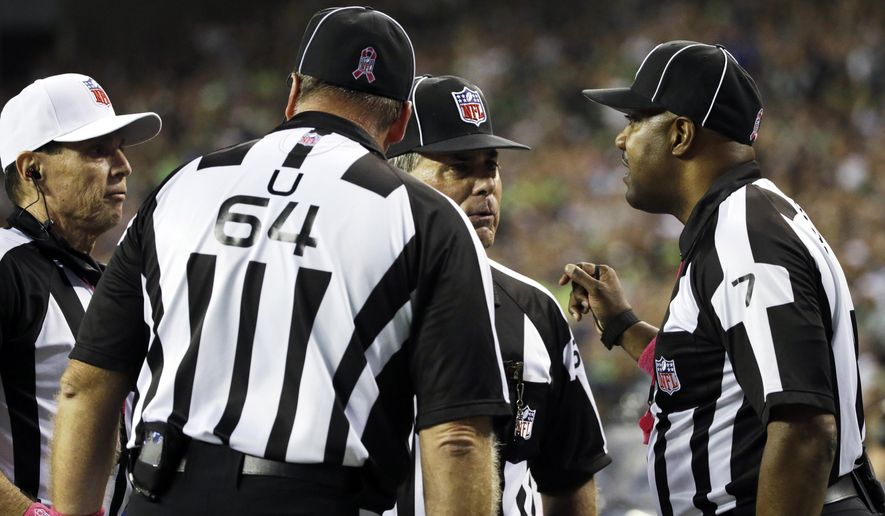 FILE - In this Oct. 5, 2015, file photo, officials, including side judge Keith Washington, right, discuss a play late in the fourth quarter of an NFL football game in Seattle, where a fumble by Detroit Lions wide receiver Calvin Johnson went out of the back of end zone and ruled a touchback. The failure to notice the Seattle Seahawks linebacker K.J. Wright clearly illegally batting the ball out of the end zone on purpose was one of several missed calls this season. (AP Photo/Elaine Thompson, File)