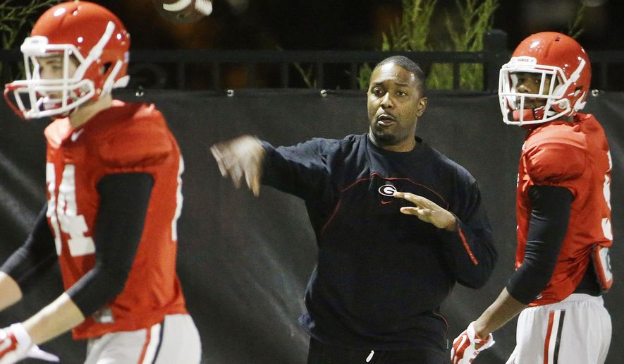 FILE- In this Dec. 16, 2015, file photo, Georgia's interim head coach Bryan McClendon, center, runs a drill during NCAA college football game in Athens, Ga. Despite having an interim coach, Georgia insists it has plenty of motivation against Penn State in the TaxSlayer Bowl. (AP Photo/David Goldman, File_