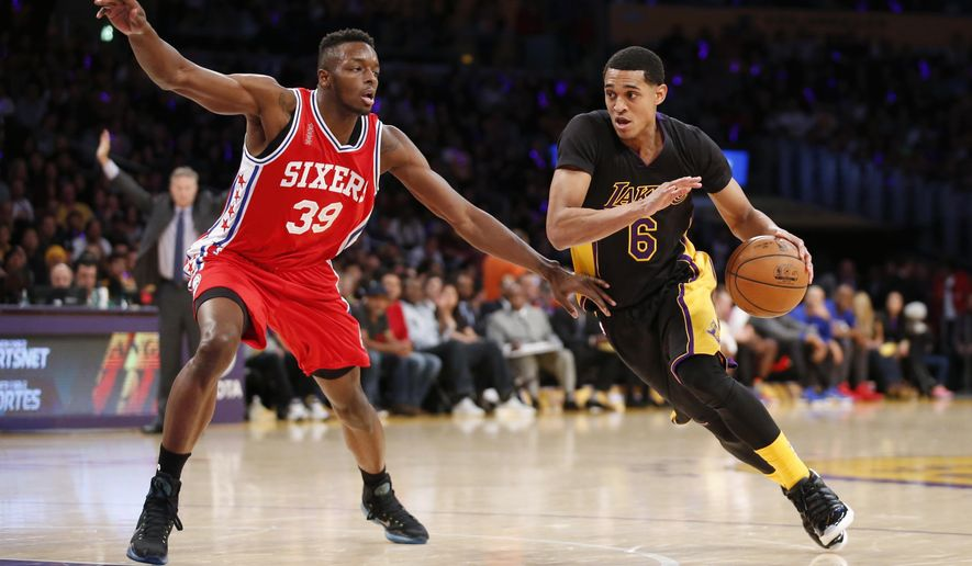 Philadelphia 76ers' Jerami Grant, left, fouls Los Angeles Lakers' Jordan Clarkson, right, during the first half of an NBA basketball game, Friday, Jan. 1, 2016, in Los Angeles. (AP Photo/Danny Moloshok)