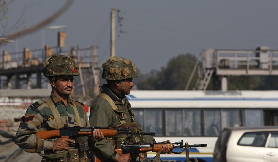 Indian army soldiers take positions outside the Indian airbase in Pathankot, 430 kilometers (267 miles) north of New Delhi, India, Saturday, Jan. 2, 2016. At least four gunmen entered an Indian air force base near the border with Pakistan on Saturday morning and exchanged fire with security forces, leaving two of them dead, officials said. (AP Photo/Channi Anand)