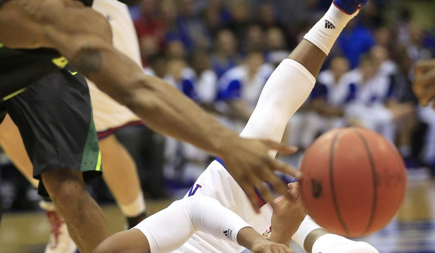 Kansas guard Devonte' Graham, bottom, passes to a teammate past Baylor guard Lester Medford, left, during the first half of an NCAA college basketball game in Lawrence, Kan., Saturday, Jan. 2, 2016. (AP Photo/Orlin Wagner)