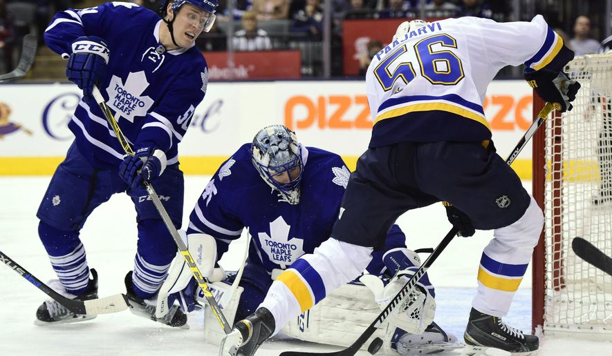 Toronto Maple Leafs goalie Jonathan Bernier makes a save on St. Louis Blues' Magnus Paajarvi (56) as Maple Leafs' Jake Gardiner (51) defends during the third period of an NHL hockey game in Toronto on Saturday, Jan. 2, 2016. (Frank Gunn/The Canadian Press via AP)