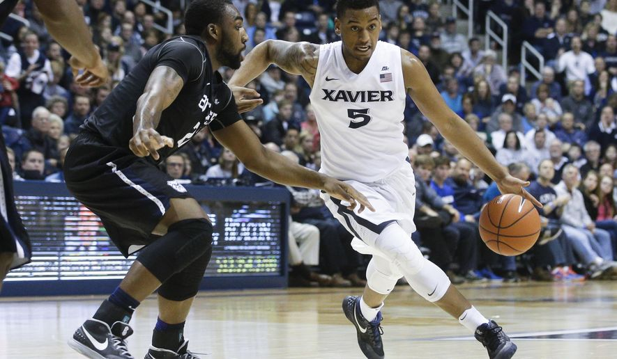 Xavier's Trevon Bluiett (5) drives around Butler's Roosevelt Jones (21) in the first half of an NCAA college basketball game, Saturday, Jan. 2, 2016, in Cincinnati. (AP Photo/John Minchillo)