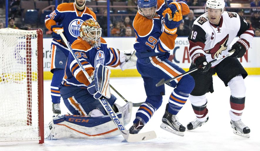 Arizona Coyotes' Shane Doan (19) battles in front with Edmonton Oilers' Justin Schultz (19) as goalie Cam Talbot (33) makes the save during first period NHL action in Edmonton, on Saturday, Jan. 2, 2016.(Jason Franson/The Canadian Press via AP)