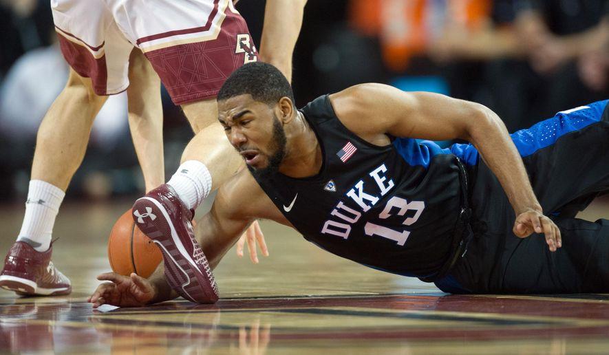 Duke guard Matt Jones (13) dives for the ball during the first half of an NCAA college basketball game Saturday, Jan. 2, 2016, in Boston. (AP Photo/Gretchen Ertl)
