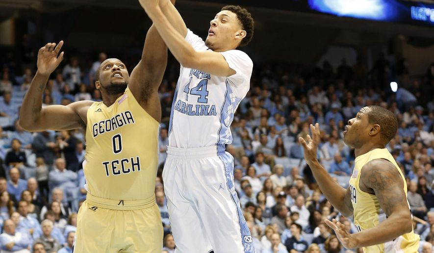 North Carolina's Justin Jackson (44) goes to the basket under pressure from Georgia Tech's Charles Mitchell (0) and Marcus Georges-Hunt, right, during the first half of an NCAA basketball game, Saturday, Jan. 2, 2016, in Chapel Hill, N.C. (AP Photo/Ellen Ozier)