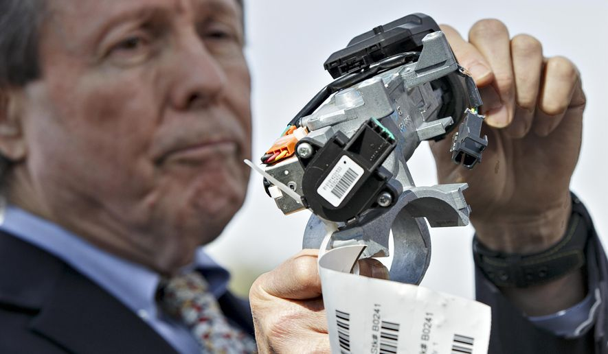 FILE - In this April 1, 2014, file photo, Clarence Ditlow, executive director of the Center for Auto Safety, displays a GM ignition switch similar to those linked to 13 deaths and dozens of crashes of General Motors small cars like the Chevy Cobalt, during a news conference on Capitol Hill in Washington. A civil trial starting January 2016 in New York City will test the legal boundaries of hundreds of claims remaining against General Motors over faulty ignition switches. (AP Photo/J. Scott Applewhite, File)
