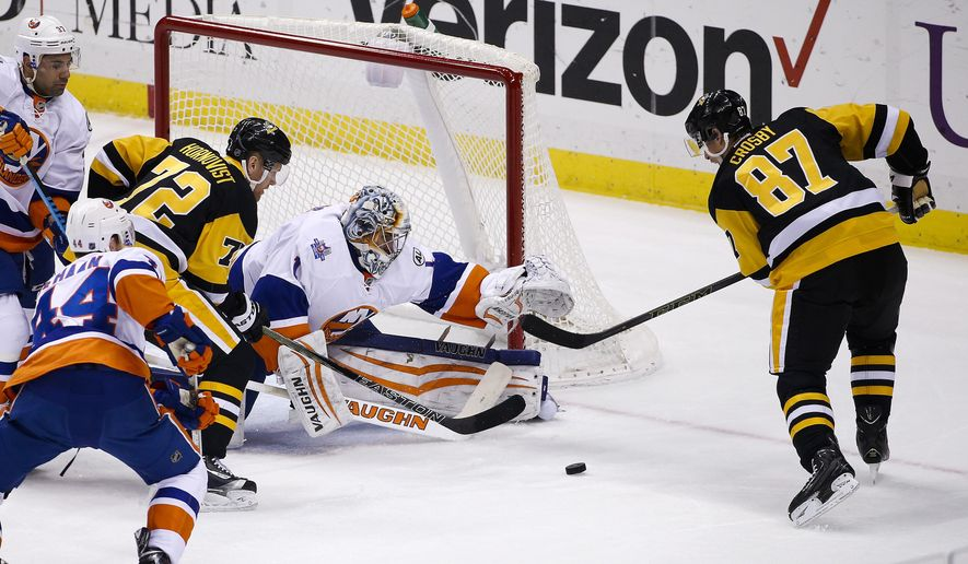 New York Islanders goalie Thomas Greiss (1) reaches for a rebound but can't get to it before Pittsburgh Penguins' Sidney Crosby (87) lifts it over him for a goal during the first period of an NHL hockey game in Pittsburgh, Saturday, Jan. 2, 2016. (AP Photo/Gene J. Puskar)