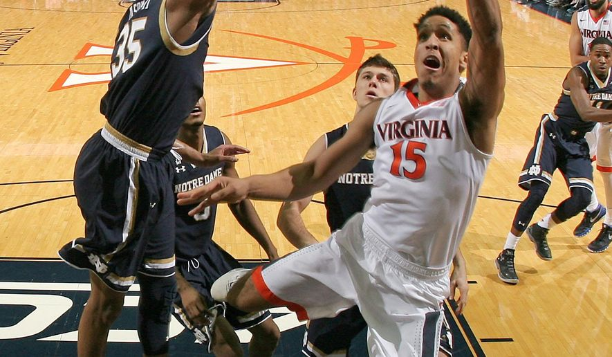 Virginia guard Malcolm Brogdon (15) shoots next to Notre Dame forward Bonzie Colson (35) during an NCAA college basketball game Saturday, Jan. 2, 2016,  in Charlottesville, Va. Virginia won 77-66. (AP Photo/Andrew Shurtleff)