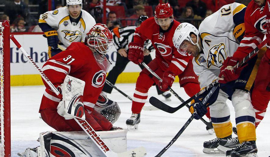 Nashville Predators' Mike Fisher (12) has his shot blocked by Carolina Hurricanes goalie Eddie Lack (31) as he is defended by Hurricanes' Justin Faulk (27) during the second period of an NHL hockey game Saturday, Jan. 2, 2016, in Raleigh, N.C. (AP Photo/Karl B DeBlaker)