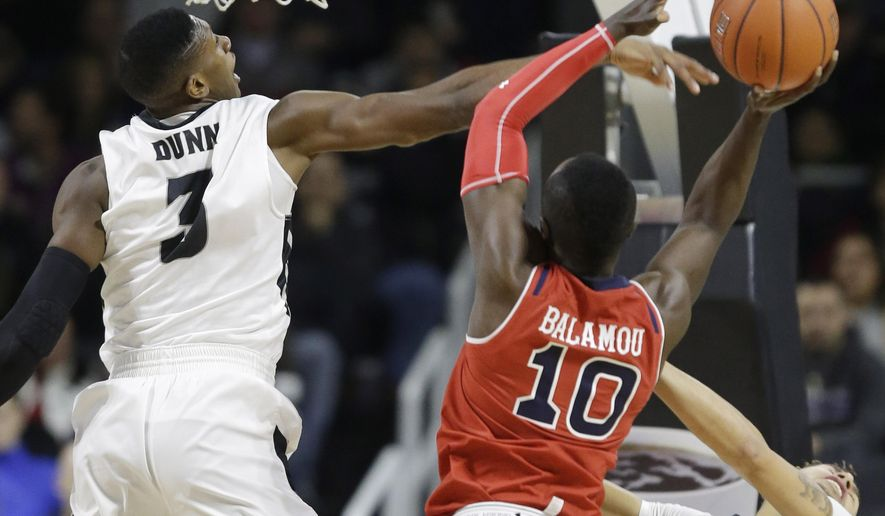 Providence guard Kris Dunn (3) deflects a shot by St. John's guard Felix Balamou (10) during the first half of an NCAA college basketball game, Saturday, Jan. 2, 2016, in Providence, R.I. (AP Photo/Stephan Savoia)