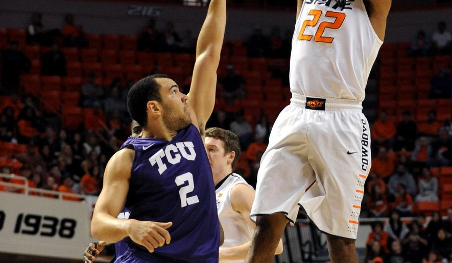 Oklahoma State guard Jeff Newberry, right, takes a shot over TCU guard Michael Williams in the first half of an NCAA college basketball game in Stillwater, Okla., Saturday, Jan. 2, 2016. Newberry scored 23 points in the 69-48 win over TCU. (AP Photo/Brody Schmidt)
