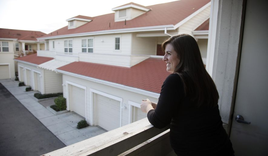 In this Dec. 11, 2015 photo, Katy Howser, a kindergarten teacher in the Santa Clara School District, looks out from the balcony of her apartment at Casa Del Maestro, an apartment complex for teachers, in Santa Clara, Calif. School districts in high cost-of-living areas and rural communities that have long struggled to staff classrooms are considering buying or building rent-subsidized apartments as a way to attract and retain teachers amid concerns of a looming shortage. (AP Photo/Marcio Jose Sanchez)