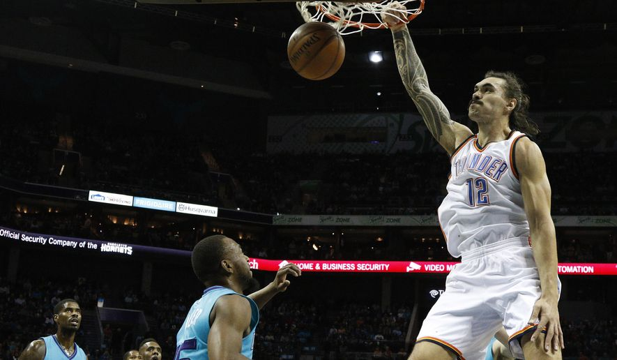 Oklahoma City Thunder's Steven Adams (12) dunks over Charlotte Hornets' Kemba Walker (15) and Marvin Williams (2) during the first half of an NBA basketball game in Charlotte, N.C., Saturday, Jan. 2, 2016. (AP Photo/Bob Leverone)