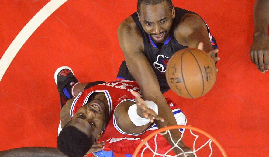 Los Angeles Clippers forward Luc Richard Mbah a Moute, right, of Cameroon, shoots as Philadelphia 76ers forward Nerlens Noel defends during the first half of an NBA basketball game, Saturday, Jan. 2, 2016, in Los Angeles. (AP Photo/Mark J. Terrill)