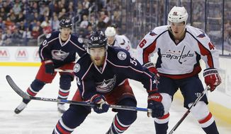 Columbus Blue Jackets' David Savard, left, and Washington Capitals' Michael Latta chase the puck during the first period of an NHL hockey game Saturday, Jan. 2, 2016, in Columbus, Ohio. (AP Photo/Jay LaPrete)