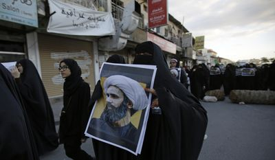 A Bahraini protester holds a picture of Saudi Shiite cleric Sheikh Nimr al-Nimr during a rally denouncing his execution by Saudi Arabia, Sunday, Jan. 3, 2016, in Daih, Bahrain. Saudi Arabia announced the execution of al-Nimr on Saturday along with 46 others. Al-Nimr was a central figure in protests by Saudi Arabia's Shiite minority until his arrest in 2012, and his execution drew condemnation from Shiites across the region. (AP Photo/Hasan Jamali)