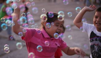 Filipino children play with bubbles at a public park as the long Christmas season holidays come to an end in this largely Roman Catholic nation on Sunday, Jan. 3, 2016, in suburban Quezon city, north of Manila, Philippines. (AP Photo/Aaron Favila)