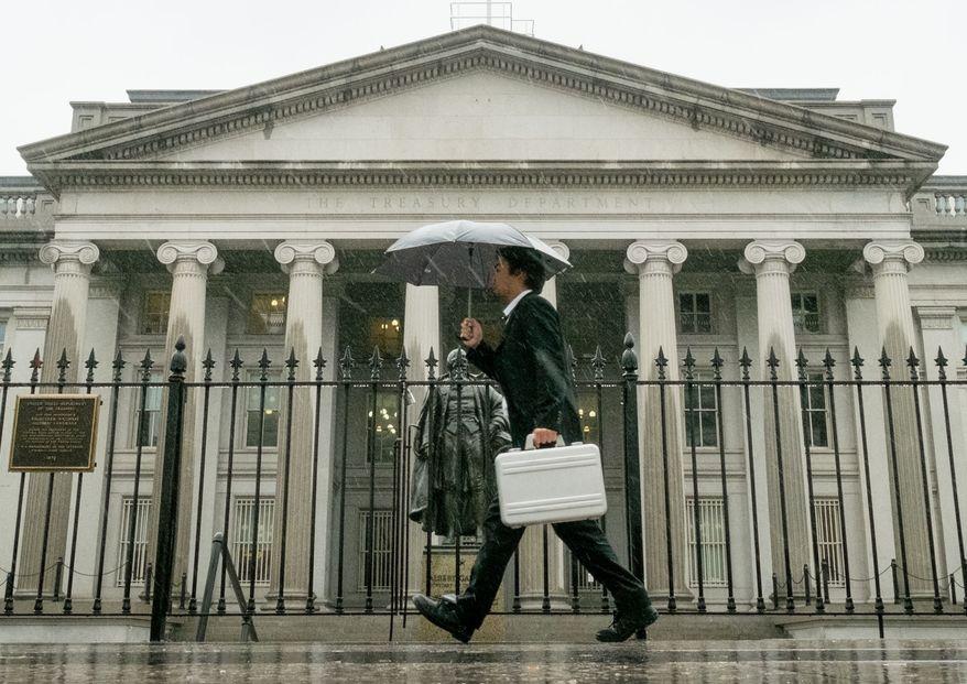 A pedestrian walks past the U.S. Treasury Building in Washington on a rainy day. (Associated Press)